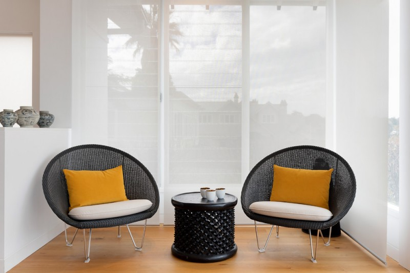 small sized contemporary sunroom black contemporary chairs with hair pin legs mustard throw pillows black finishing center table in cylinder shape medium toned wood floors