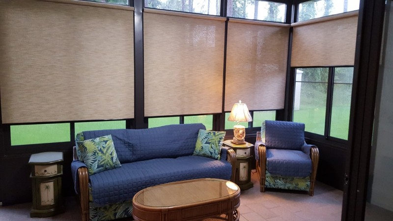 sunroom with roller shades blue sofa blue chair glass top wood coffee table