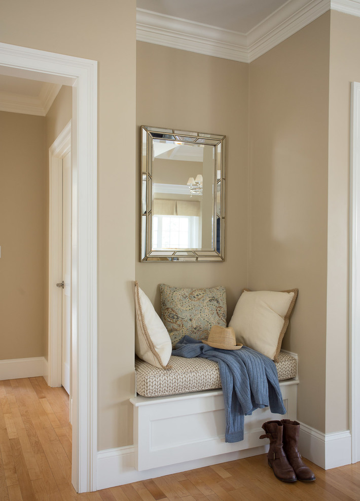 traditional hallway small bench some throw pillows chrome framed mirror light toned wood floors cream walls