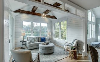traditional sunroom design white wood siding walls medium toned wood floors exposed wood beams light grey furniture set light grey rug black finishing side tables