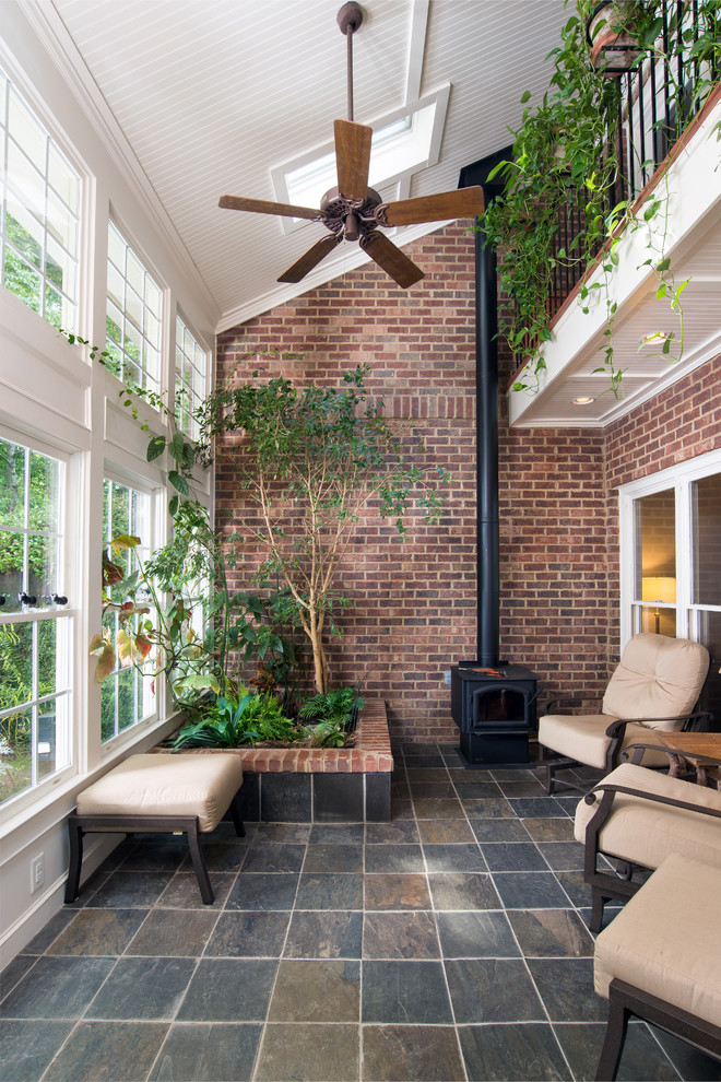 traditional sunroom idea red brick walls dark tiled floors beige furniture set permanent planter outdoor fireplace in black