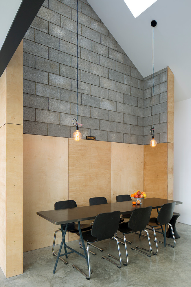 urban style dining room drop light fixtures mid century modern dining furniture set in black halfway wood grey brick walls glossy coated concrete floors
