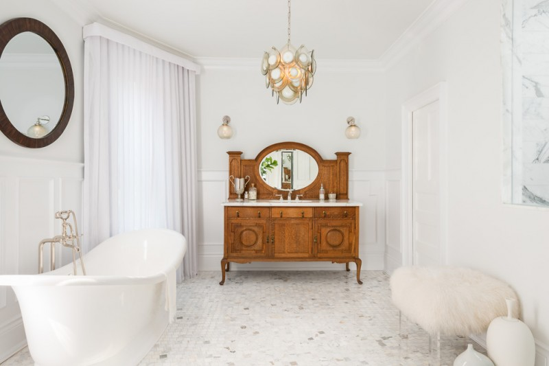 victorian style bathroom idea medium toned wood bathroom vanity with marble countertop round mirror white tiles floors white bathtub white window curtains