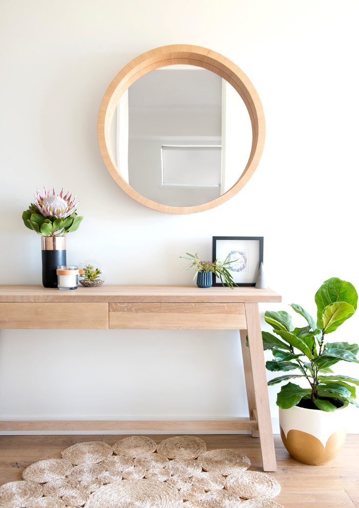 Scandinavian style hallway light wood hall console table with angled legs light wood floors little greens light wood framed round mirror white walls