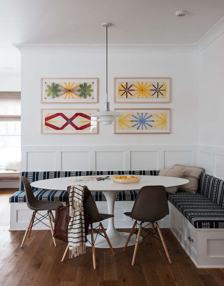 centered gallery wall with colorful artworks L shaped built in dining bench with storage mid century modern plastic chairs with angled legs modern pendant large & round top table in white