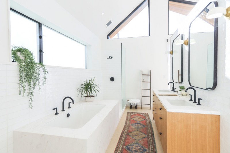 clean lines bathroom with black details walk in shower with glass door panels decorative ladder rack marble top vanity with medium toned wood cabinets built in bathtub in white Morrocan rug light wood