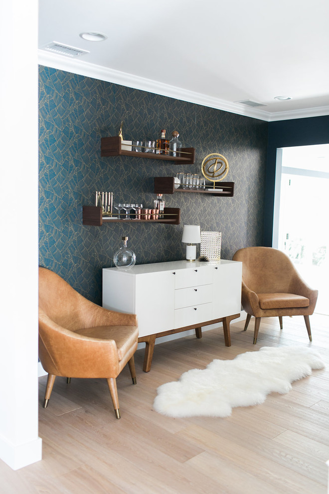 clean lines white freestanding with angled wood legs leather armchairs with angled legs light wood floors fluffy white rug floating shelves with front rail blue wallpaper with gold line accents