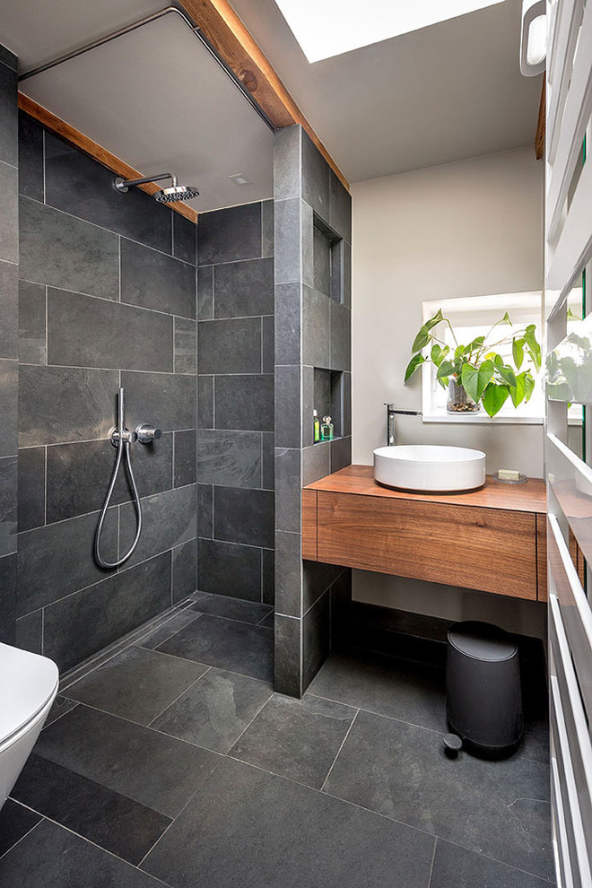 contemporary bathroom hardwood bathroom vanity with white sink dark tiles floors and walls recessed shelves walk in shower light grey walls