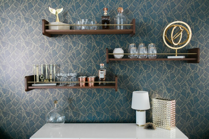 dark wood floating shelves with front rail vintage style wallpaper in blue accented by gold lines