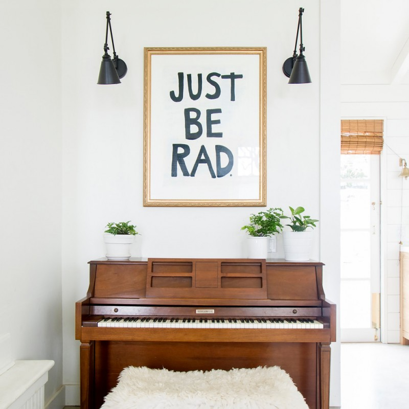 eclectic music corner grand piano with darker wood finishing oversize frame wall decor mini pots for greens white walls a couple of wall lamps with black shades