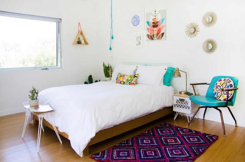 eclectic scandinavian bedroom white comforter white metal side table with wood surface purple rug with geometric patterns medium toned wood floors white walls turquoise armchair