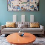 Mid Century Modern Living Room Flintstones Painting Covington Blue Painting Walls Grey Couch With Tufted Back Multicolored Throw Pillows Round Top Coffee Table In Orange Color Blue White Area Rug