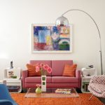 Midcentury Modern Living Room Red Couch Orange Throw Pillows Sponged Orange Rug Clear Acrylic Coffee Table Contemporary Side Tables In White Abstract Painting