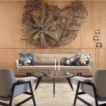 Modern Style Living Room Creative Wall Decor Made Of Wire And Metal Soft Earthy Brown Couch Dark Throw Pillows With Bright Accents Glass Top Round Coffee Table Witn Pointed Legs Light Brown Fabric Rug