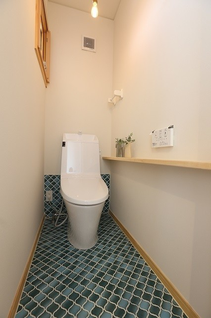 narrow modern bathroom blue mosaic tiles floors white toilet white painted walls with wood accents