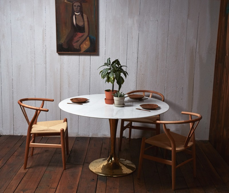 organic wood dining chairs in modern vintage white round top dining table with gold base whitewashed wood siding walls dark wood floors