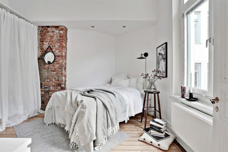 scandinavian bedroom white walls light wood floors bare brick wall light grey bed treatment grey bed rug darker wood side table