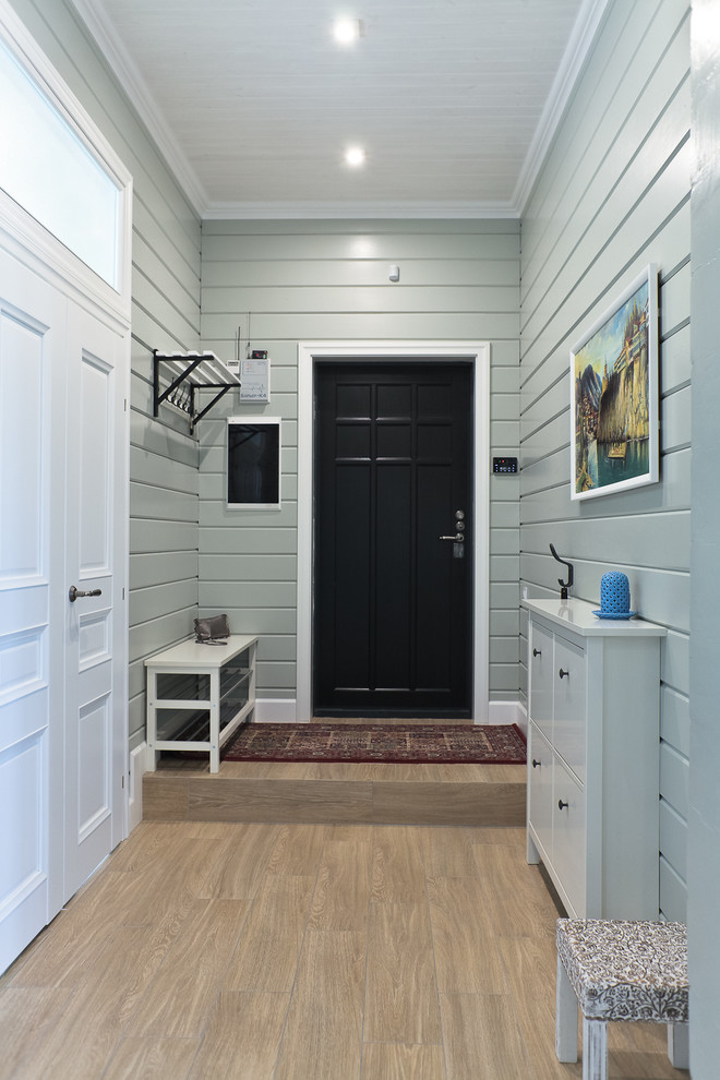 scandinavian entry hall light wood floors light grey wood siding walls black painted front door white hall cabinets white benh