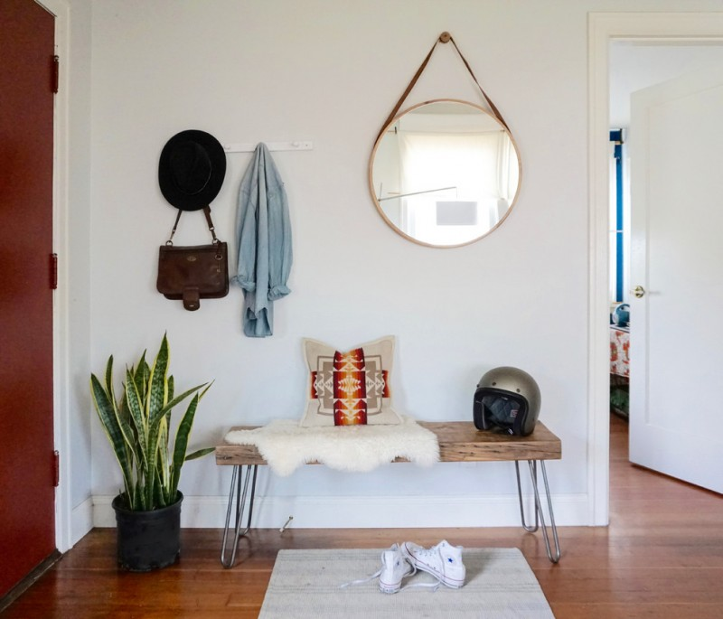 scandinavian entryway hairpin metal legs bench white shoe mat medium toned wood floors corner decorative plants hanging round shaped mirror