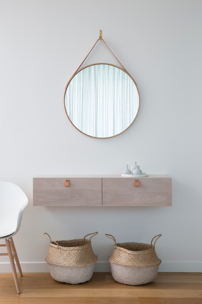 scandinavian hallway idea floating light wood hall console thin framed mirror in round shape two decorative baskets angled wood legs chair