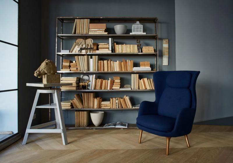 scandinavian home library medium sized book rack bold blue armchair lighter blue walls light wood floors