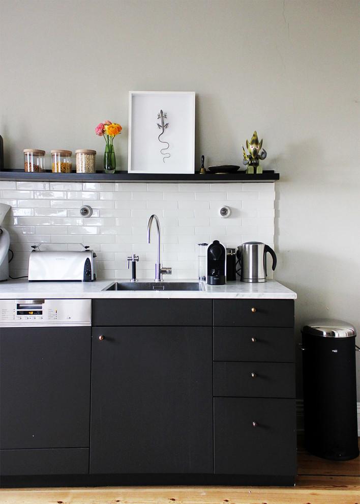 scandinavian kitchen design black doff cabinets white countertop white subway tiles backsplash light wood floors white floors