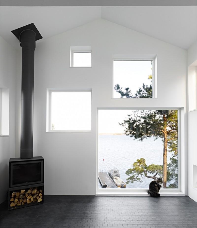 scandinavian living room white walls square shaped glass windows black tiles floors black stained wood burner