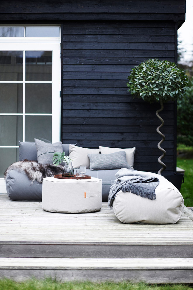 scandinavian patio idea white and grey bean bags white center table solid black wood siding exterior walls white trimmed window spiral stand decorative plant
