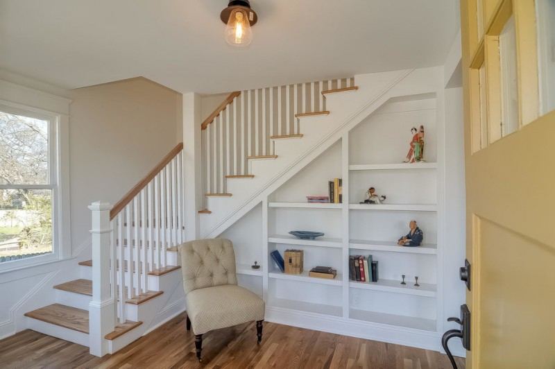 shabby chic entryway white built in bookshelves vintage style chair in beige medium toned wood floors white staircase with wooden steps and railings