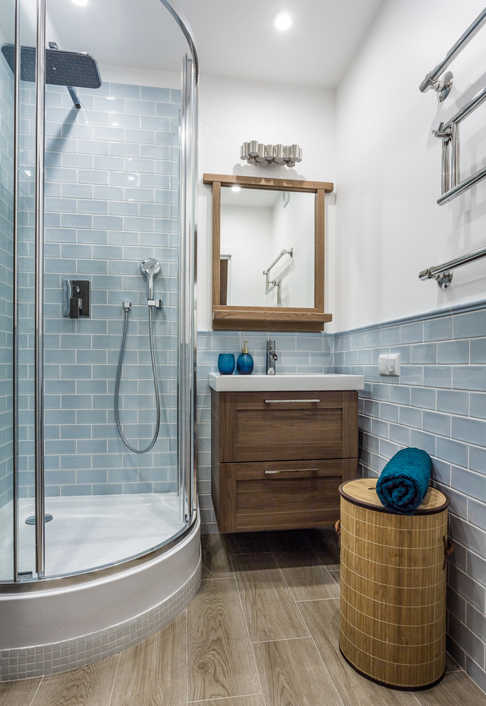 small bathroom in beach style aquatic blue tiles walls half curved walk in shower wood vanity with farmhouse sink wood woven basket storage wood floors