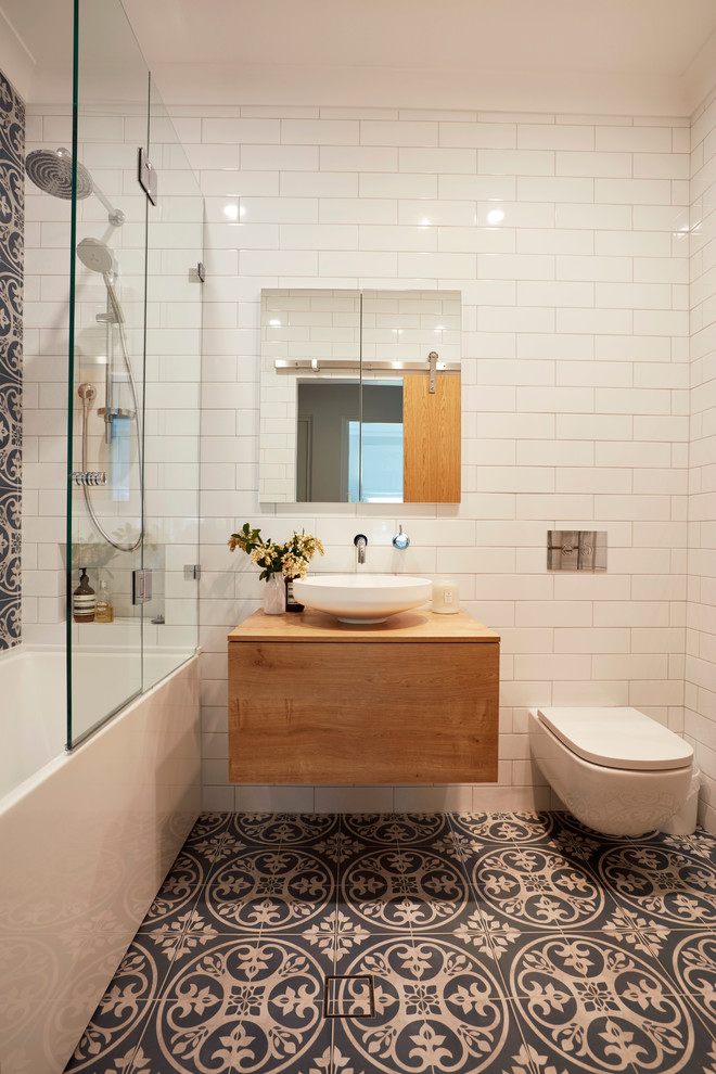 small contemporary bathroom patterned wall tile floors floating wood bathroom vanity with white vessel frameless mirror with storage behind wall hung toilet in white white subway tiled walls