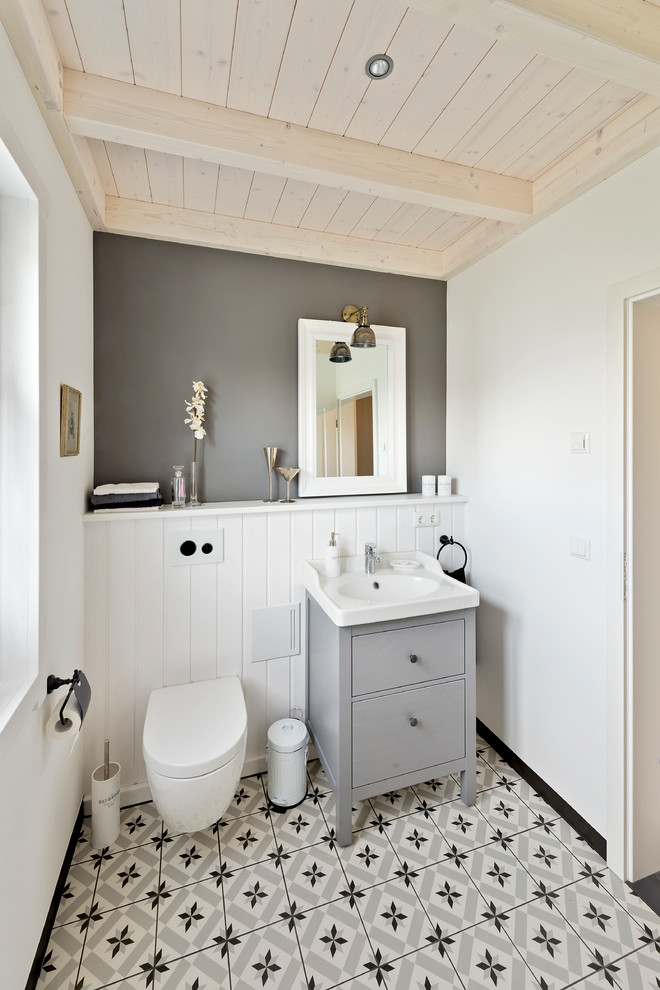 small country style bathroom light grey bathroom vanity with undermount sink in white porcelain tiled floors wall mounted toilet in white vertical wood siding walls