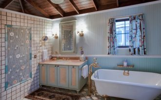 small eclectic bathroom in traditional style freestanding bathtub in white with gold toned shower fixtures blue finish bathroom vanity with cream top undermount sink terracotta tiles floors and side w