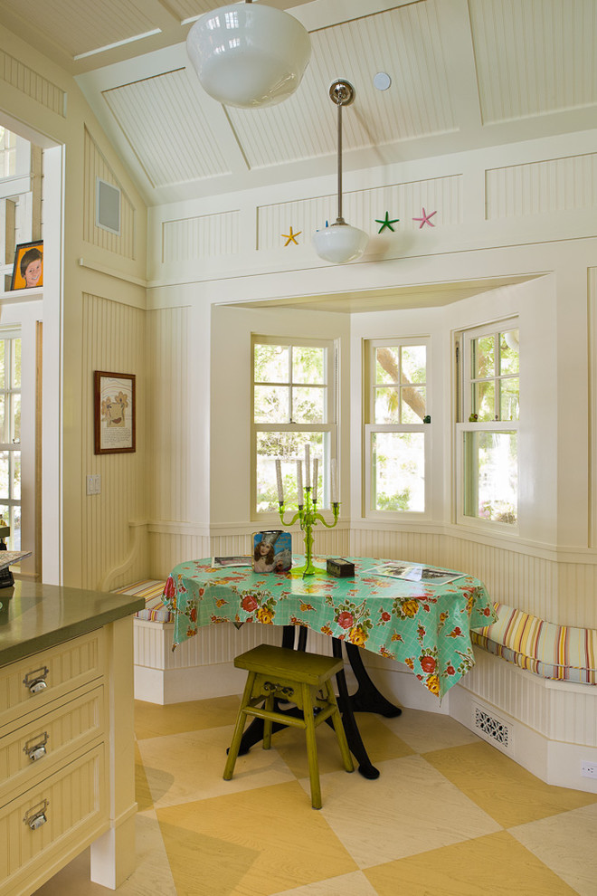 small farmhouse style breakfast nook built in bench dark wood table with green flowery skirt side chair