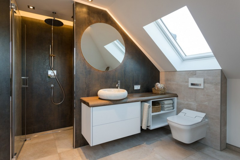 small modern bathroom floating bathroom vanity with wood countertop floating toilet dark wood walls with large and round mirror cream tiles floors skylight