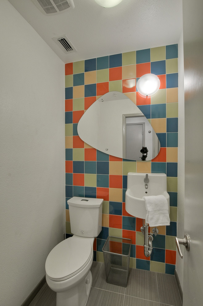 small modern bathroom mix colorful tiles wall background amoeba shaped mirror smaller wall mounted sink white toilet
