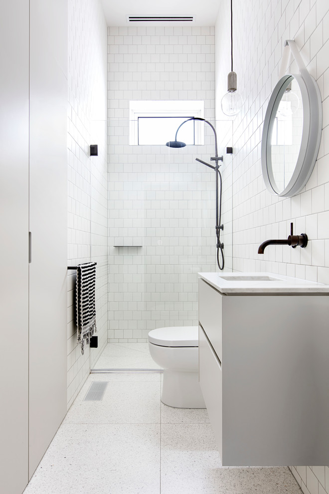 small scandinavian bathroom white ceramic subway tiles walls white ceramic tiles floors white toilet floating white vanity with undermount sink round framed mirror