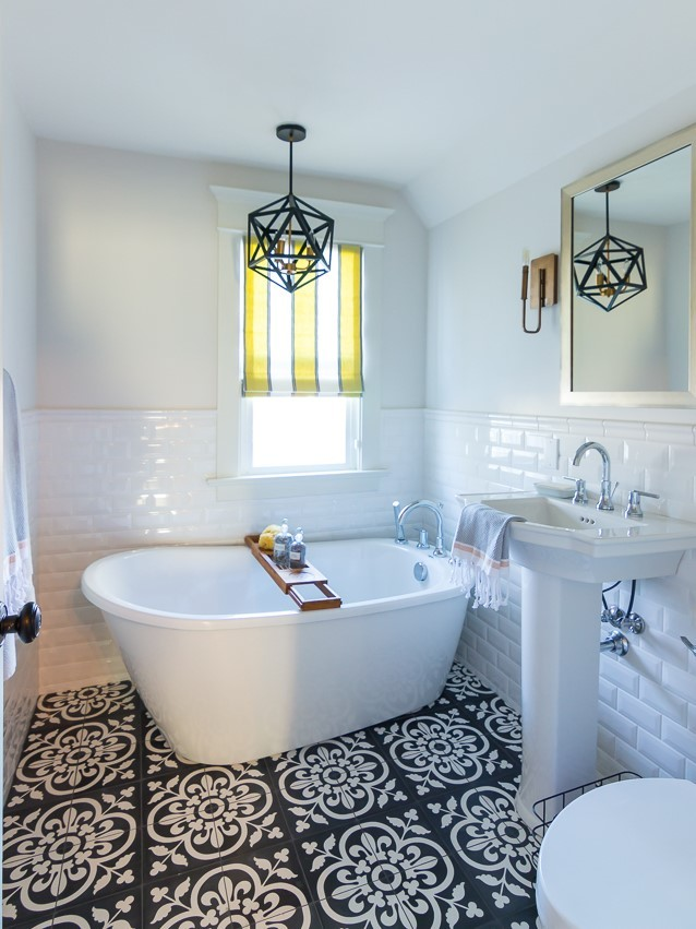 small sized traditional bathroom flower patterned tiles floors freestanding bathtub in white subway tiles walls white pedestal sink gold framed mirror black wrought iron pendant pop of yellow window b