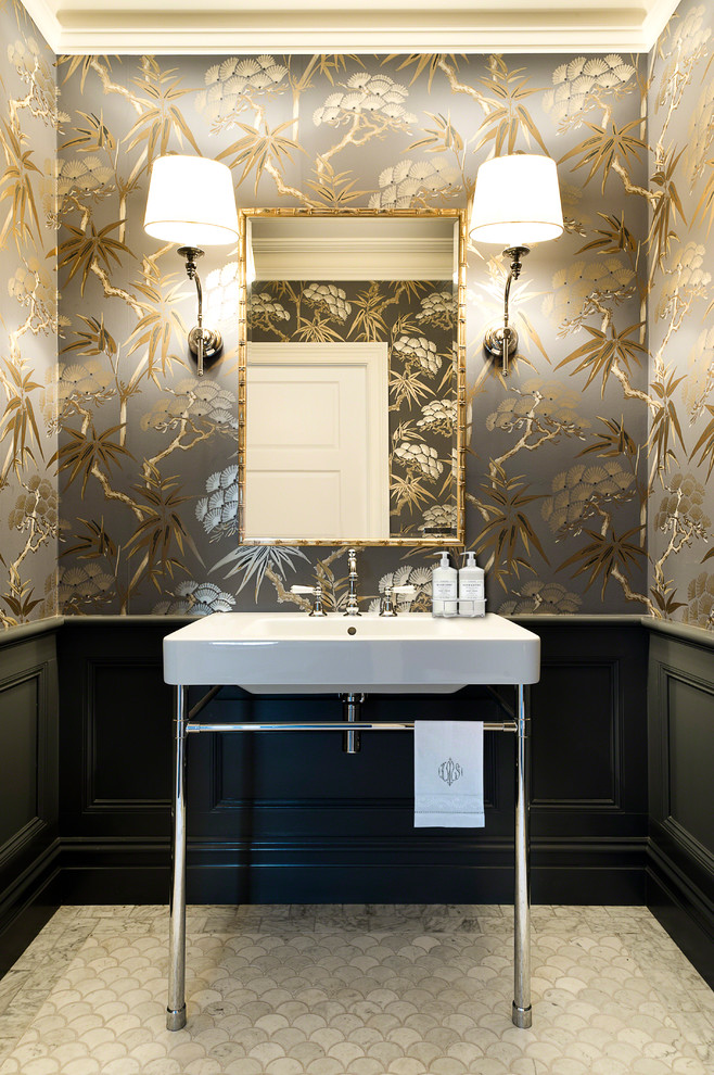 small traditional bathroom glowing gold floral wallpaper white pedestal sink with chrome legs black baseboard a pair of wall mounted lights gold framed mirror