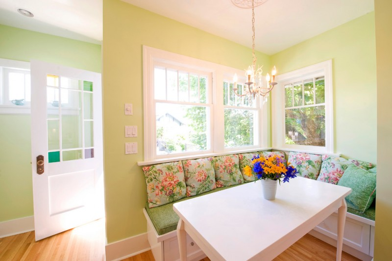 stylish breakfast nook light green walls white trimmed windows L shaped bench seat green vintage throw pillows with flower motifs white table colorful ornate flowers traditional chandelier