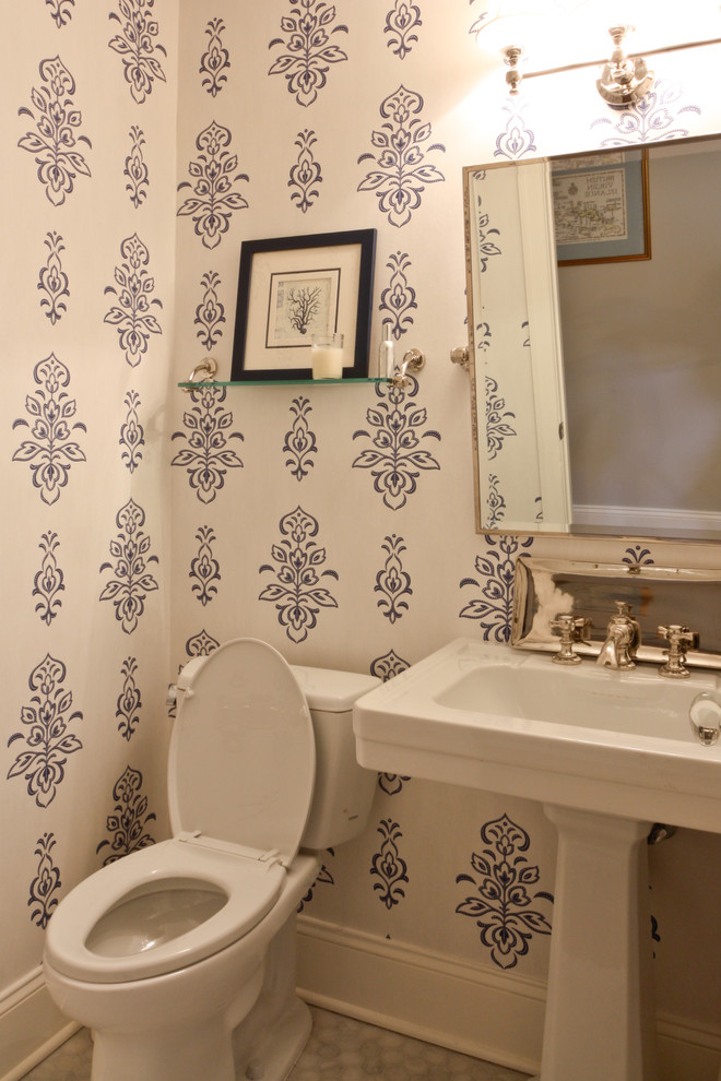 traditional bathroom idea classic floral wallpaper in white and navy blue white pedestal sink white hexagon tiled floors white toilet