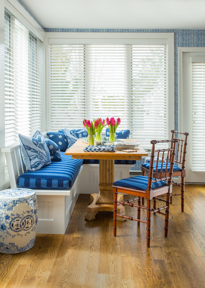 traditional breakfast nook L shaped bench seat with comfy blue seater blue throw pillows wooden table bamboo chairs medium toned wood floors