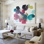 Transitional Living Room Soft Toned Couch With Facing Chaise And Throw Pillows Abstract Picture With Playful Colors Glass Coffee Table With Gold Edge Accents