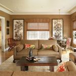 Asian styled family room warm toned sofa dark wood coffee table bamboo window blinds a pair of floral hand paintings dark wood credenza medium toned wood floors