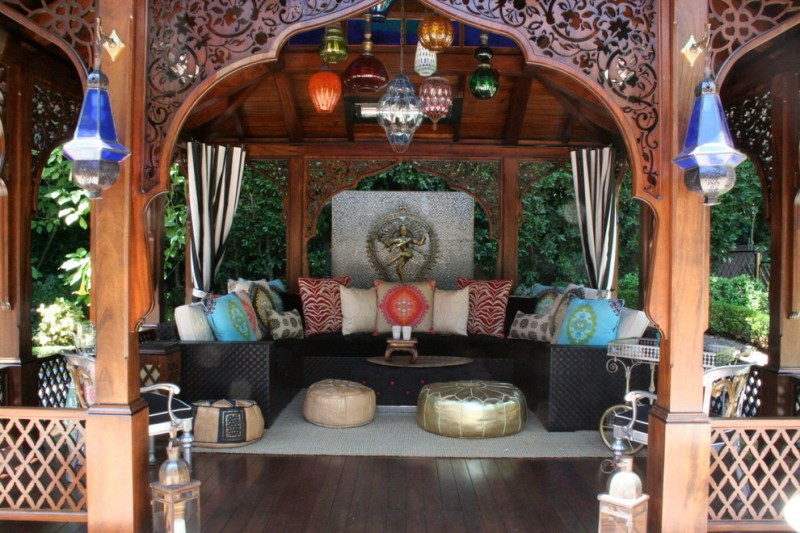 Moroccan style patio with handcrafted & arched doors colorful Moroccan lanterns curved black couch gold toned ottomans dark wood floors