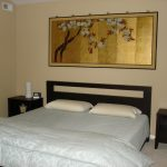 asian style guest room simple light blue linen gold toned artwork cream wall color black finish bed frame black finish bedside tables