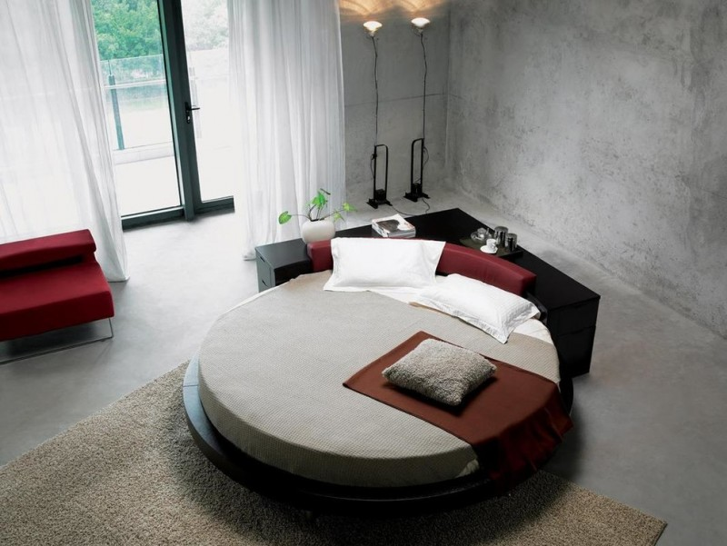 black round platform bed in contemporary style L shaped dresser in black concrete walls modern floor lamps modern red couch grey shug area rug