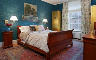 blue wallpaper gold toned antique chinese cabinets wooden bed frame with curly headboard wooden bedside tables traditional rug nature view hand painting with thin frame wall mounted lamps