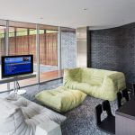 contemporary family room light green floor couch light grey floor couch light green table wooly area rug in grey vibrate black brick walls