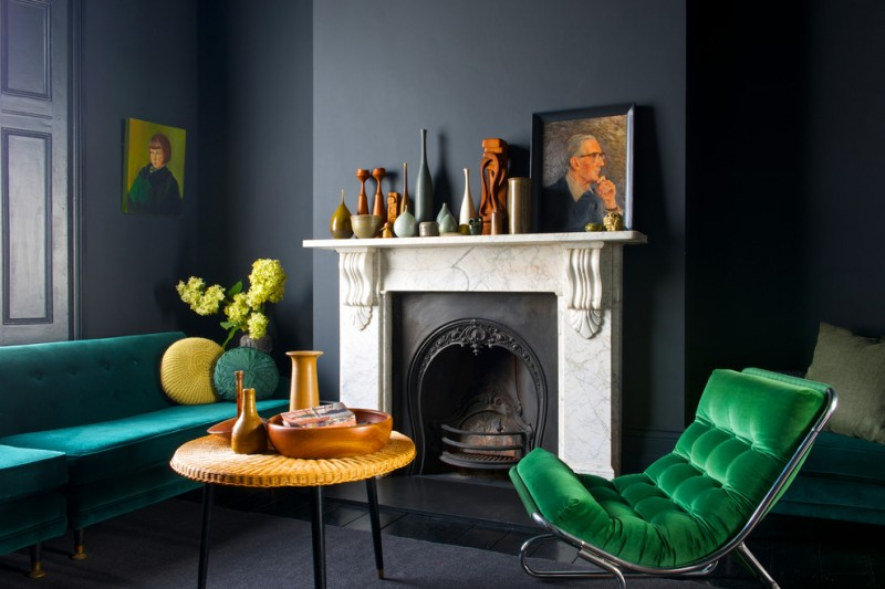 contemporary living room deep grey painted walls marble fireplace's frame pop of green couch pop of blue couch mustard yellow round top table lots of ornaments